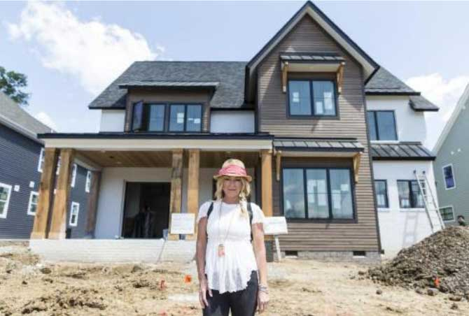 person standing in front of newly constructed home