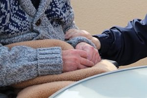 elderly person sitting in a sweater and blanket with a reassuring hand on their arm
