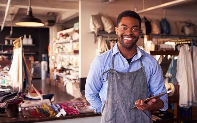 person in shop wearing an apron and holding a tablet with a square card reader attached