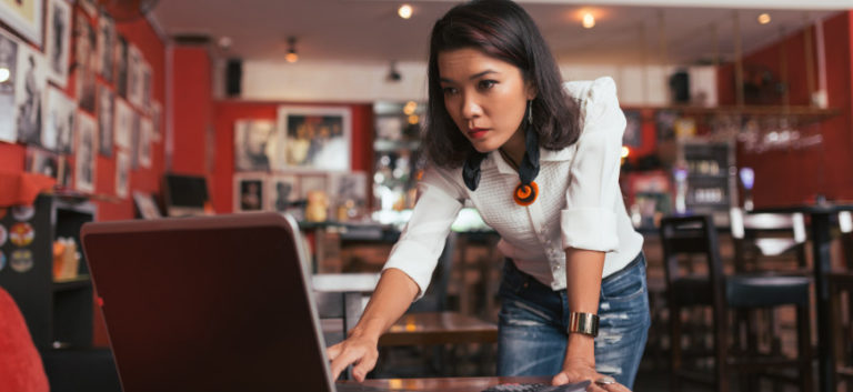 person in restaurant using computer for business banking