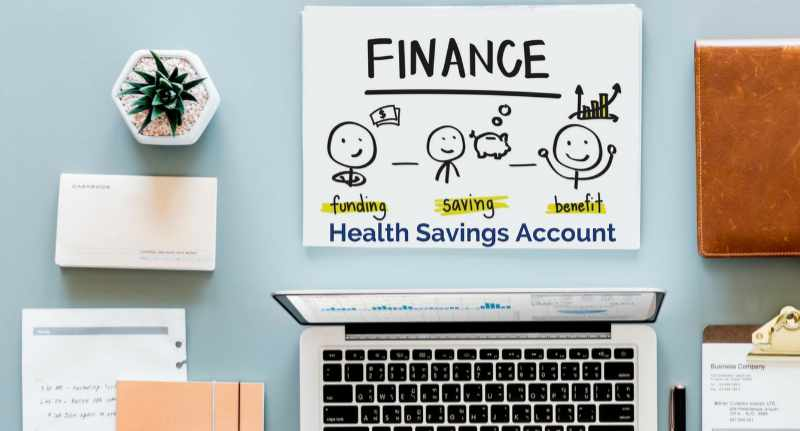 laptop and office supplies with a poster that says health savings account